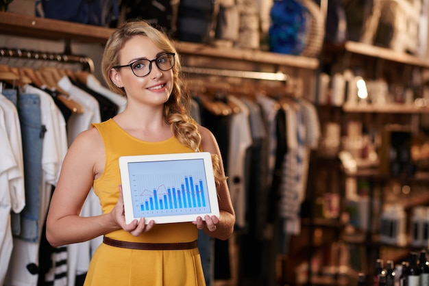 Junge kaukasische frau, die im butikenshop steht und tablette mit geschäftsdiagramm zeigt