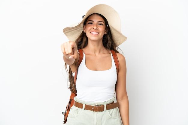 Junge kaukasische frau, die in den sommerferien eine pamela trägt, die auf weißem hintergrund isoliert ist, zeigt mit einem selbstbewussten ausdruck mit dem finger auf sie