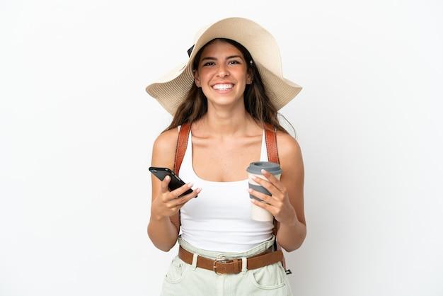 Junge kaukasische frau, die in den sommerferien eine pamela trägt, isoliert auf weißem hintergrund, die kaffee zum mitnehmen und ein handy hält