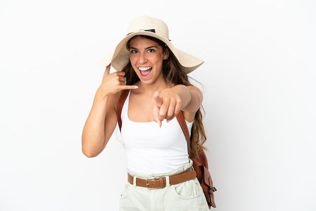Junge kaukasische frau, die in den sommerferien eine pamela trägt, isoliert auf weißem hintergrund, die telefongeste macht und nach vorne zeigt