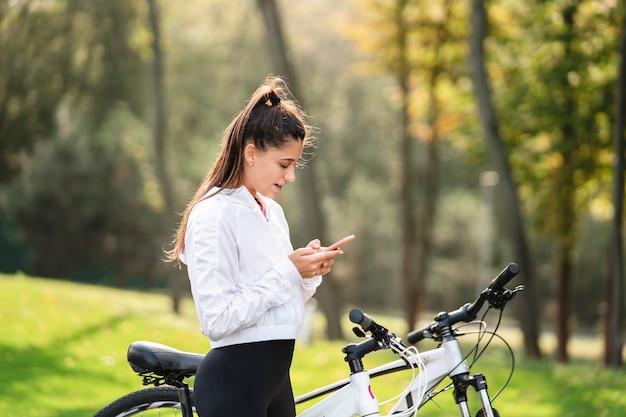 Junge kaukasische frau, die in einem park ruht, benutzt ein mobiltelefon.