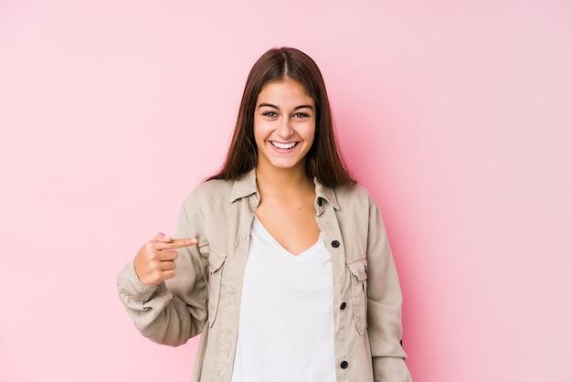 Junge kaukasische frau, die in einer rosa hintergrundperson aufwirft, die von hand auf einen hemdkopierraum zeigt, stolz und zuversichtlich