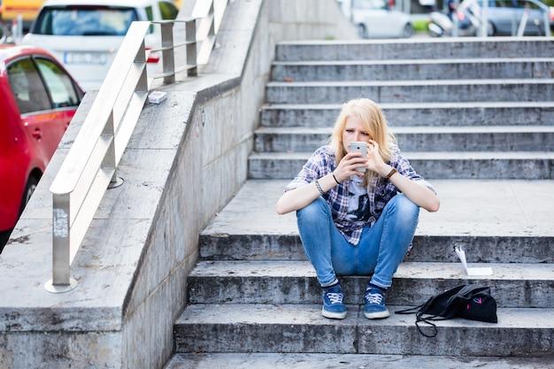 Junge kaukasische frau, die intelligentes telefon beim sitzen auf treppe verwendet