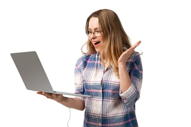 Junge kaukasische frau, die laptop, geräte, geräte lokalisiert auf weißer wand verwendet. konzept moderner technologien, gadgets, technik, emotionen, werbung. exemplar. reden, online-bildung treffen.