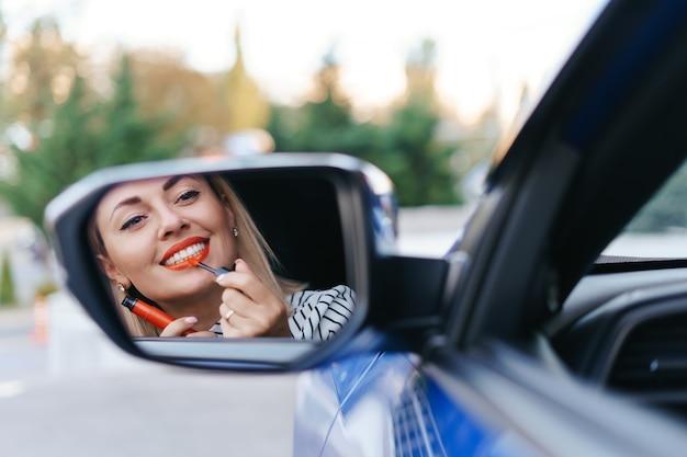 Junge kaukasische frau, die lippenstift anwendet, der reflexion im autospiegel betrachtet.
