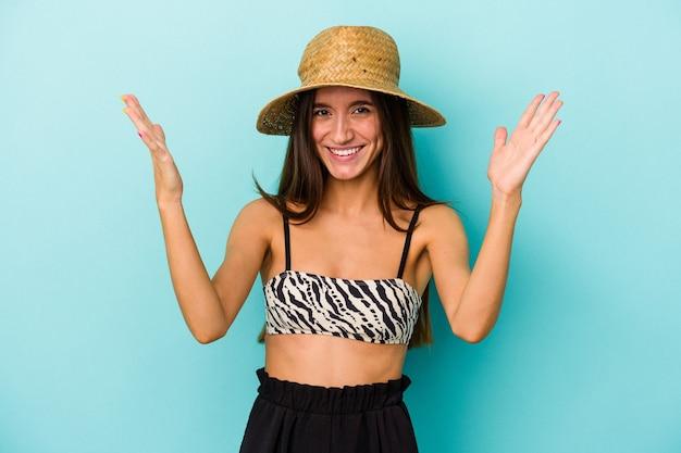 Junge kaukasische frau, die mit bikini an den strand geht, einzeln auf blauem hintergrund, eine angenehme überraschung, aufgeregt und die hände hebend.