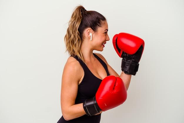Junge kaukasische frau, die mit boxhandschuhen lokalisiert auf weißem hintergrund kämpft