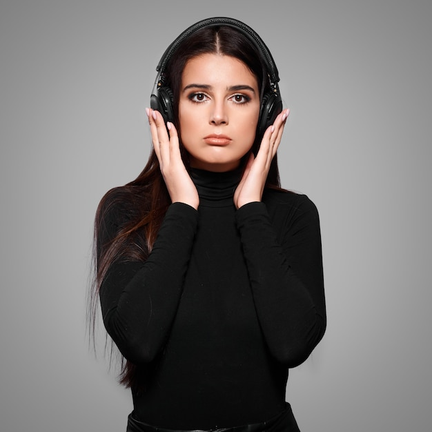 Junge kaukasische frau, die musik in drahtlosen kopfhörern auf lokalisiertem hintergrund hört