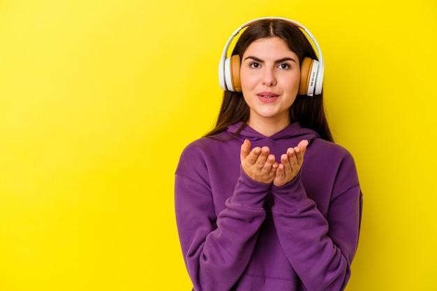 Junge kaukasische frau, die musik mit kopfhörern auf rosa faltlippen hört und palmen hält, um luftkuss zu senden.