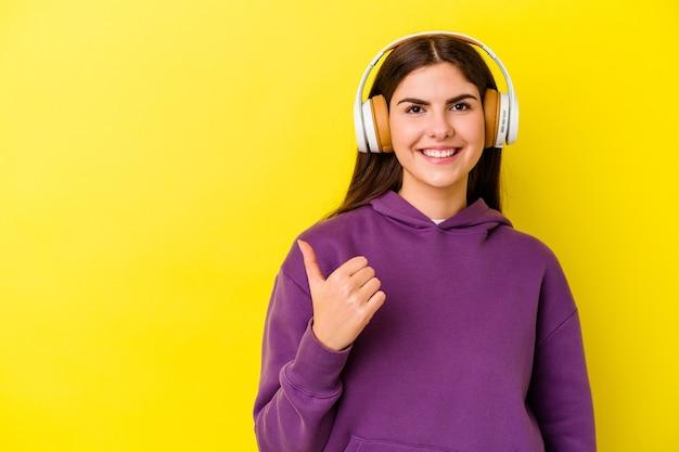 Junge kaukasische frau, die musik mit kopfhörern lokalisiert auf rosa wandlächeln und daumen hochheben hört