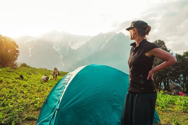 Junge kaukasische frau, die nahe einem zelt steht und im schönen sonnenlicht durchnässt