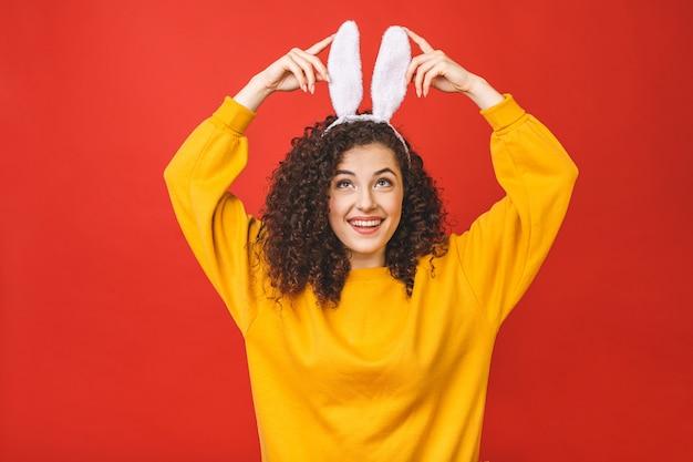 Junge kaukasische frau, die niedliche osterhasenohren über rotem lokalisiertem hintergrund trägt, während sie zuversichtlich und glücklich lächelt.