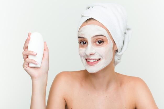 Junge kaukasische frau, die offacial maskenbehandlung mit einer feuchtigkeitscremeflasche genießt
