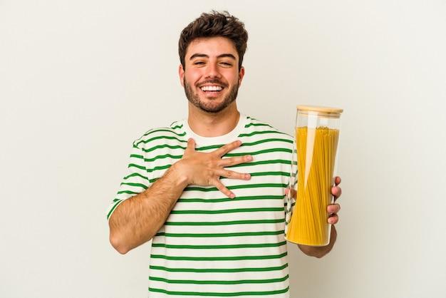 Junge kaukasische frau, die pasta-glas isoliert auf weißem hintergrund hält, lacht laut und hält die hand auf der brust.