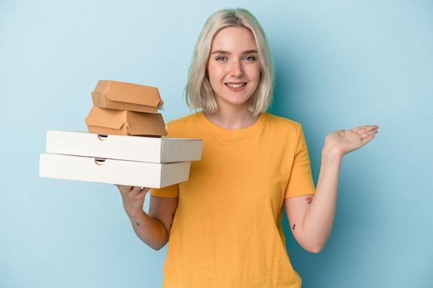 Junge kaukasische frau, die pizza und burger einzeln auf blauem hintergrund hält, die einen kopienraum auf einer handfläche zeigt und eine andere hand an der taille hält.