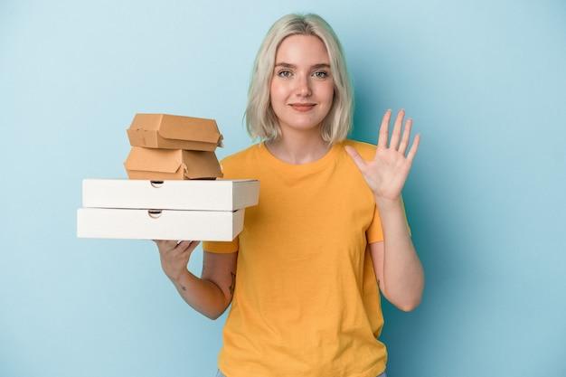 Junge kaukasische frau, die pizza und burger einzeln auf blauem hintergrund hält, lächelt fröhlich und zeigt nummer fünf mit den fingern.