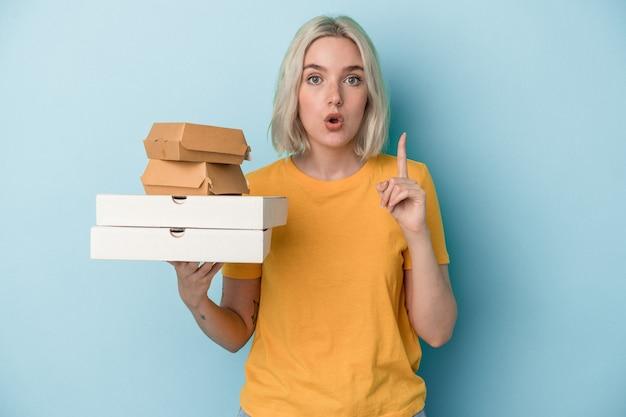 Junge kaukasische frau, die pizza und burger einzeln auf blauem hintergrund hält und eine großartige idee hat, konzept der kreativität.