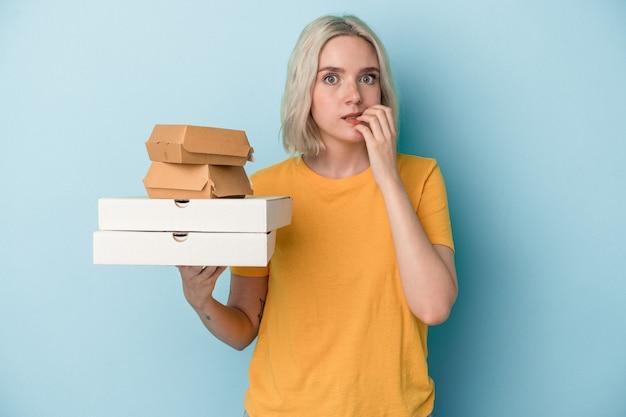 Junge kaukasische frau, die pizza und burger einzeln auf blauem hintergrund hält und fingernägel beißt, nervös und sehr ängstlich.