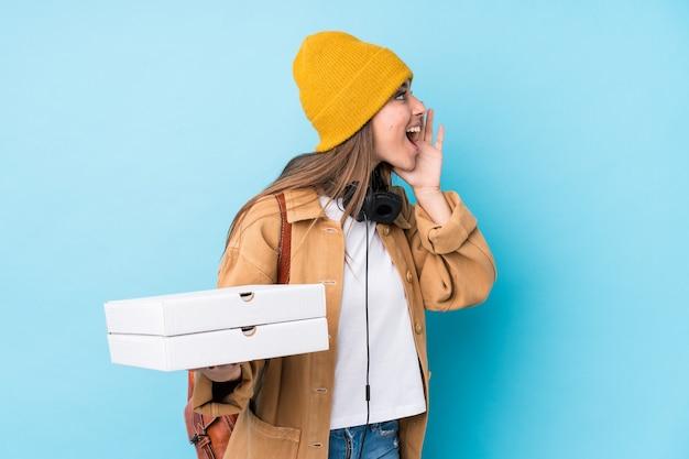 Junge kaukasische frau, die pizzas isoliert schreit und handfläche nahe geöffnetem mund hält.