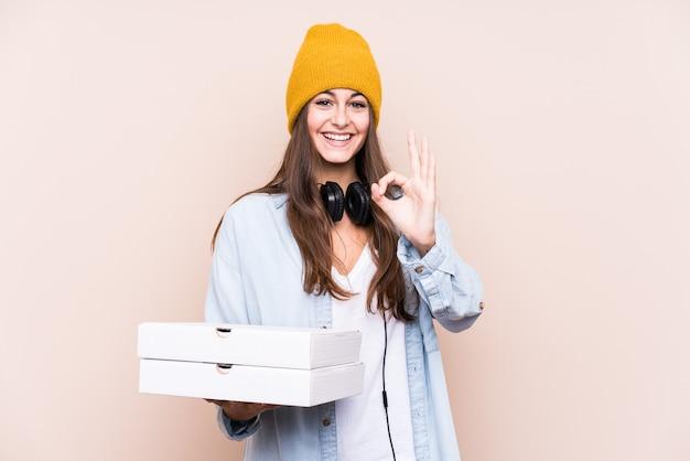 Junge kaukasische frau, die pizzas lokalisiert fröhlich und zuversichtlich zeigt, ok geste zeigend.