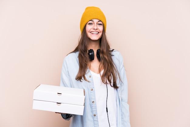 Junge kaukasische frau, die pizzen lokalisiert glücklich, lächelnd und fröhlich hält.