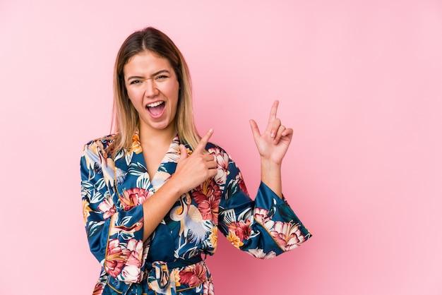 Junge kaukasische frau, die pyjamas trägt, die mit zeigefingern auf eine leere stelle zeigen und aufregung und verlangen ausdrücken.