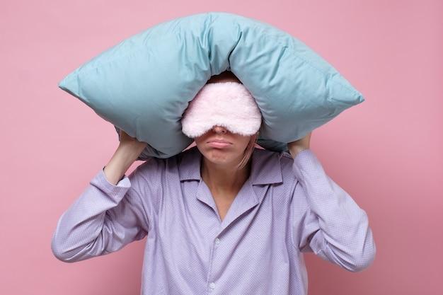 Junge kaukasische frau, die schlafmaske beim schlafen hält ein kissen trägt.