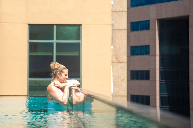 Junge kaukasische frau, die sich in einem pool auf dem dach eines wolkenkratzers in einer metropole unter der sonne entspannt....