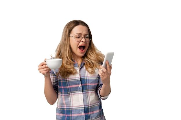 Junge kaukasische frau, die smartphone, geräte, gadgets lokalisiert auf weißer wand verwendet. konzept moderner technologien, gadgets, technik, emotionen, werbung. exemplar.