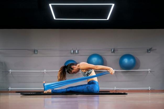 Junge kaukasische frau, die stabile elastische bandübungen der pilates-fitness in einem modernen fitnessstudio ausübt.