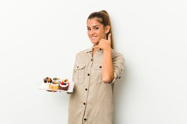 Junge kaukasische frau, die süße kuchen hält, die eine handy-anrufgeste mit den fingern zeigen.