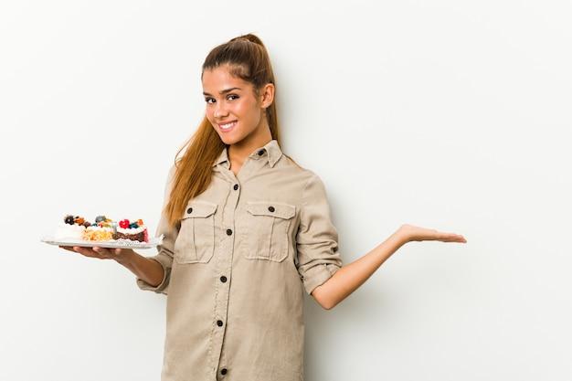 Junge kaukasische frau, die süße kuchen hält, die einen kopienraum auf einer handfläche zeigen und eine andere hand auf taille halten.
