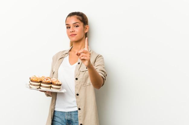 Junge kaukasische frau, die süße kuchen hält, die nummer eins mit finger zeigen.