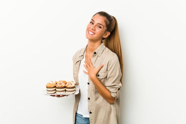 Junge kaukasische frau, die süße kuchen hält, lacht laut und hält hand auf brust.