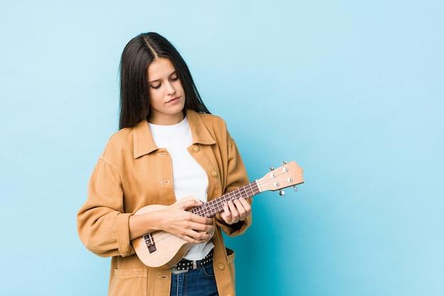 Junge kaukasische frau, die ukelele spielt, lokalisiert auf einer blauen wand