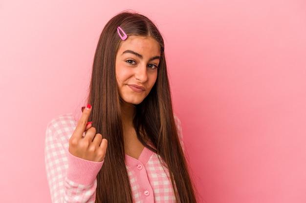 Junge kaukasische frau einzeln auf rosafarbenem hintergrund, die mit dem finger auf sie zeigt, als ob sie einladen würde, näher zu kommen.