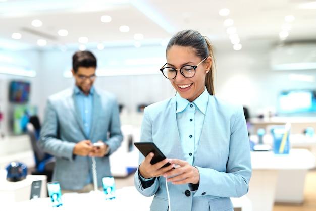 Junge kaukasische frau gekleidet im anzug, der neues smartphone ausprobiert. tech store interieur.