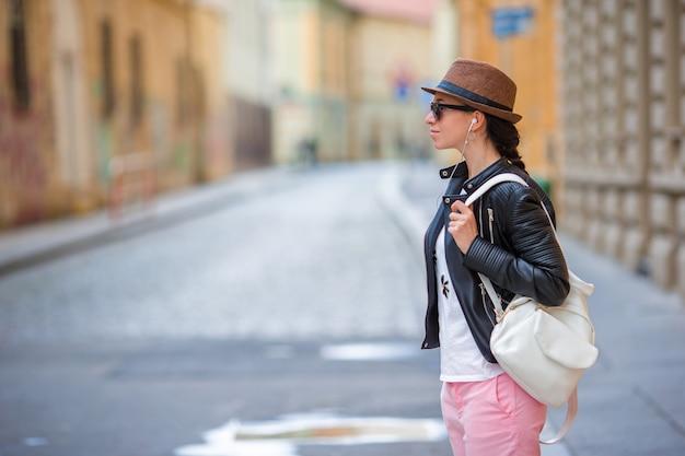 Junge kaukasische frau hören musik in der europäischen stadt draußen