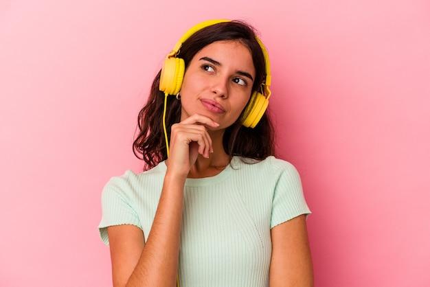 Junge kaukasische frau hört musik einzeln auf rosafarbenem hintergrund, die seitlich mit zweifelhaftem und skeptischem ausdruck schaut.