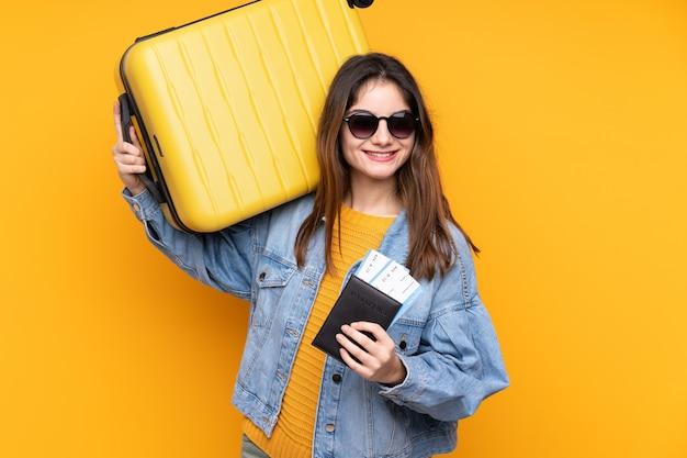 Junge kaukasische frau im urlaub mit koffer und pass