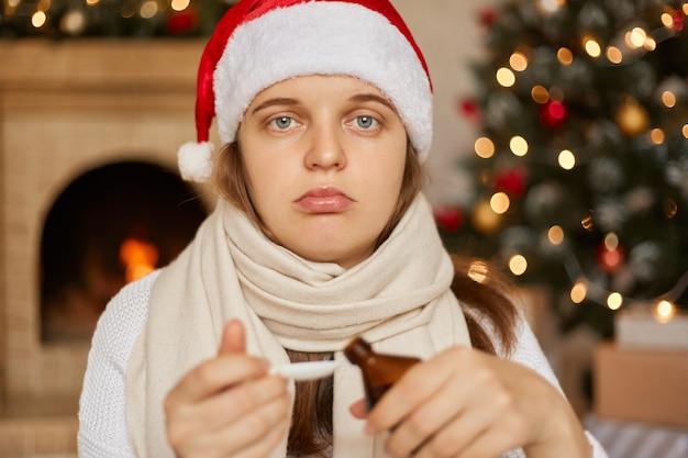 Junge kaukasische frau im weihnachtshut mit sirup vom husten, krank wegen virus oder infektion, mit verärgertem ausdruck, eingewickelt mit kriegsschal, posiert im raum mit neujahrsdekorationen