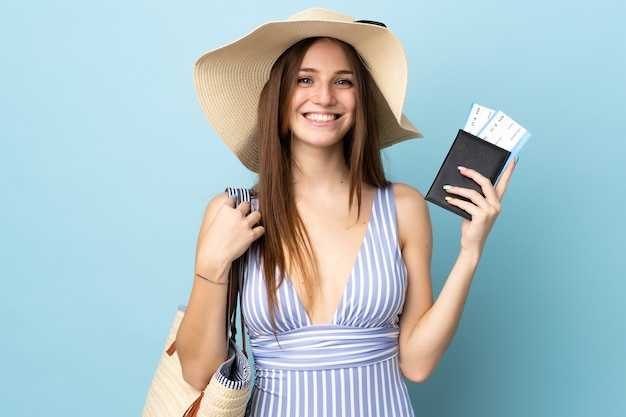 Junge kaukasische frau in den sommerferien, die den pass auf blauem hintergrund isoliert hält und viel lächelt