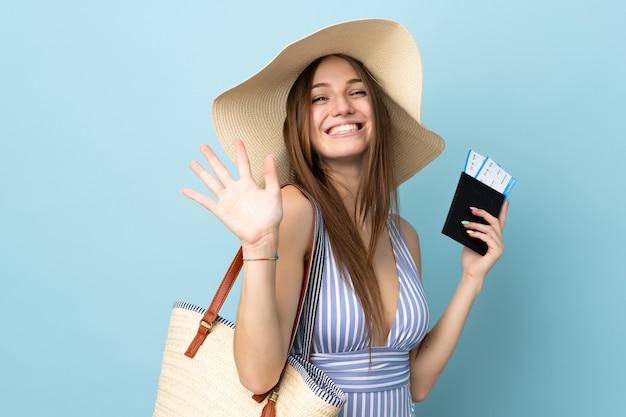 Junge kaukasische frau in den sommerferien, die den reisepass isoliert auf blauem hintergrund hält und mit der hand mit glücklichem ausdruck grüßt