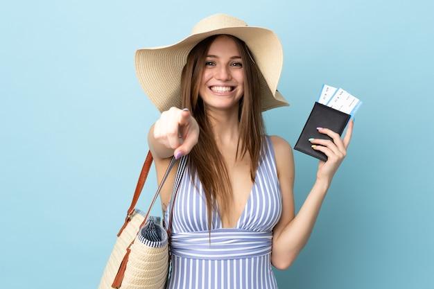 Junge kaukasische frau in den sommerferien, die einen auf blauem hintergrund isolierten reisepass hält, zeigt mit einem selbstbewussten ausdruck mit dem finger auf sie