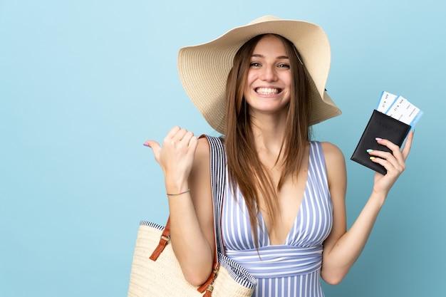 Junge kaukasische frau in den sommerferien, die einen reisepass einzeln auf blauem hintergrund hält und auf die seite zeigt, um ein produkt zu präsentieren