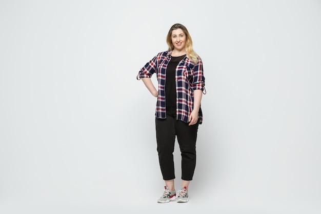 Junge kaukasische frau in der freizeitkleidung. körper positive weibliche figur, plus größe geschäftsfrau