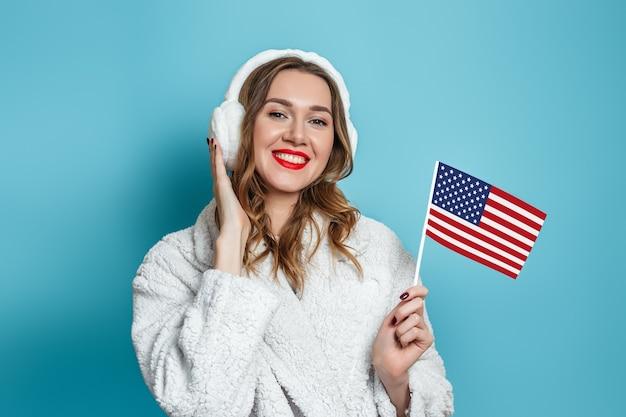 Junge kaukasische frau in einem faux weißen pelzmantel lächelt und hält eine kleine amerikanische flagge lokalisiert gegen eine blaue wand.