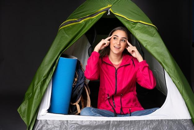 Junge kaukasische frau in einem grünen zelt des campings