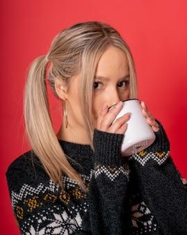 Junge kaukasische frau in einem niedlichen pullover, der tee sitzt, der gegen einen roten hintergrund sitzt