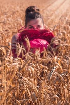 Junge kaukasische frau in einem schönen roten kleid, das das sonnige wetter in einem weizenfeld genießt
